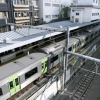 A temporarily halted train on the Yamanote loop line is seen Sunday at Meguro Station in Tokyo. | KYODO
