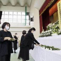 Bereaved families of the victims of a July mudslide in Atami, Shizuoka Prefecture, lay flowers at a ceremony held Sunday, 100 days after the incident. | KYODO