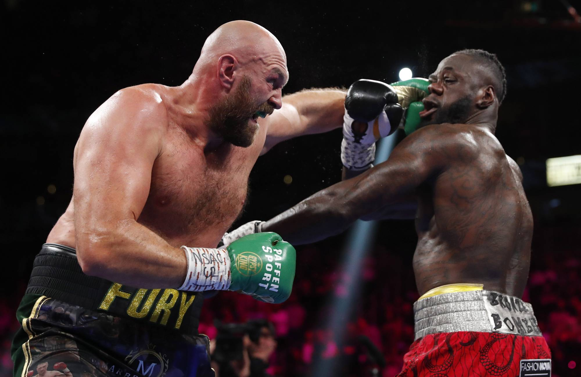 Tyson Fury (left) punches Deontay Wilder during their WBC heavyweight title bout on Saturday in Las Vegas. | REUTERS