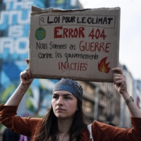 A protester holds a placard reading 'Climate law, Error 404, We are at war against inactive governments' during a demonstration against climate change in Brussels, ahead of the COP26 climate summit.    AFP-JIJI