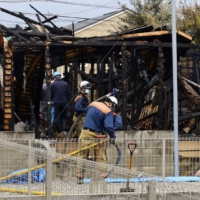 Firefighters Tuesday investigate a house in Kofu, Yamanashi Prefecture, which was burned down in a suspected arson.   KYODO