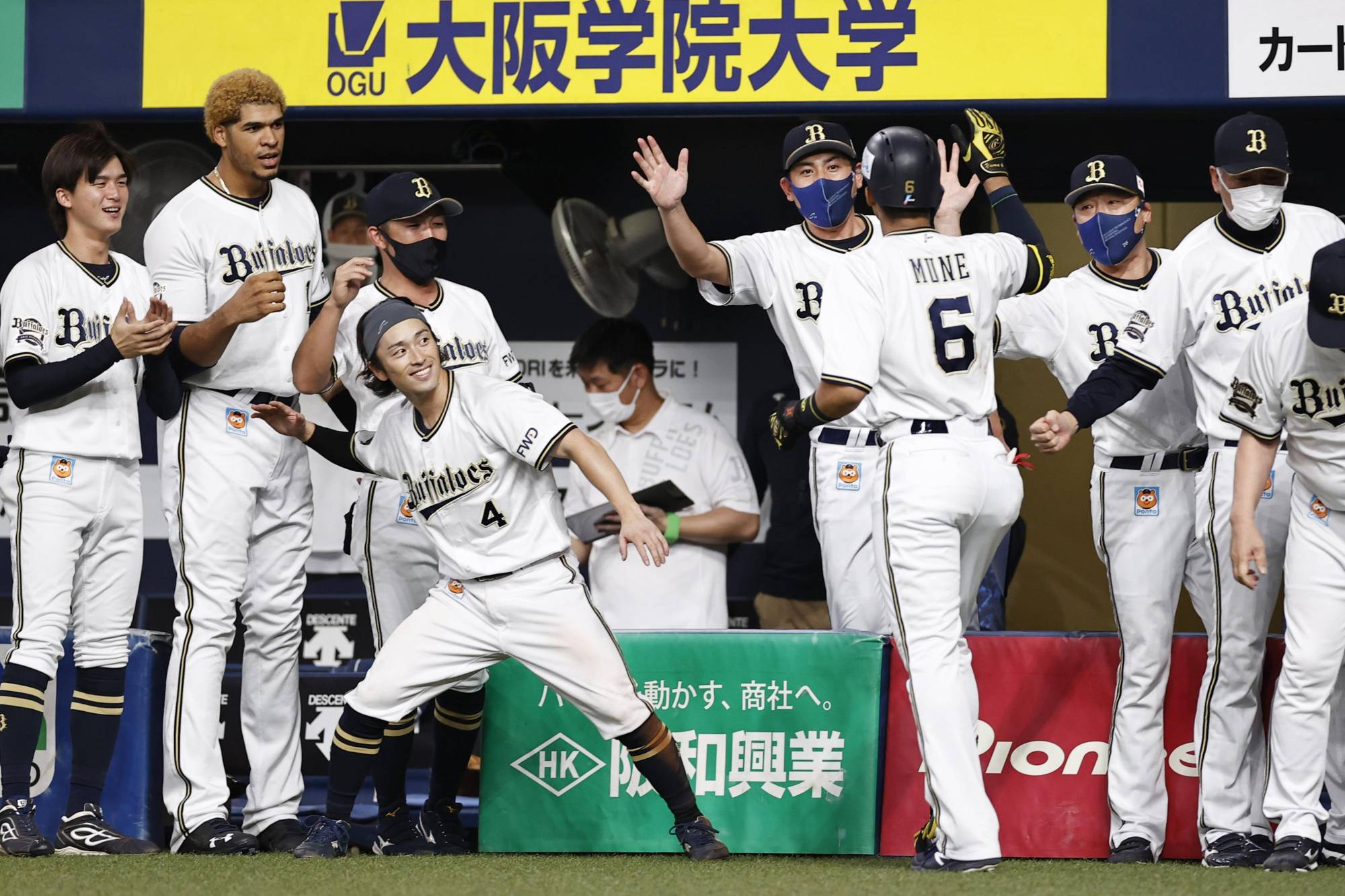 Yuma Mune (6) celebrates at the Orix dugout after hitting a game-tying home run in the eighth inning against the Marines on Tuesday in Osaka.   KYODO
