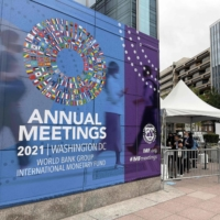 People wait outside the entrance to the annual meetings of the World Bank and International Monetary Fund outside the IMF headquarters in Washington on Monday. | AFP-JIJI