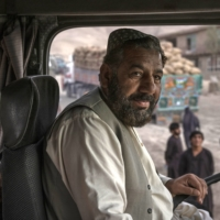Abdul Basir Fisrat in his truck in Kabul. Fisrat has made do without an education and driven under five different governments since the 1980s, two of them ruled by the Taliban.   VICTOR J. BLUE / THE NEW YORK TIMES