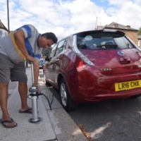 Uber driver Tim Win demonstrates plugging his fully electric Nissan Leaf into an on-street residential electric vehicle charging system developed by startup Trojan Energy in London.    REUTERS