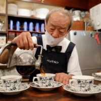 Shizuo Mori, the owner of Heckeln coffee shop, pours coffee into a cup at his shop in Tokyo. | REUTERS
