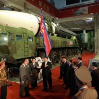 North Korean leader Kim Jong Un speaks to officials as weapons and vehicles, including the country's largest intercontinental ballistic missile (back left), loom in the background at the 'Defense Development Exhibition' in Pyongyang in this undated photo released Tuesday.   KCNA / VIA REUTERS