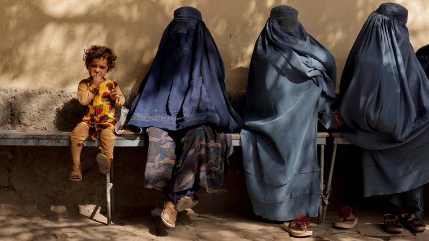 A girl sits with women outside a hospital in Kabul on Oct. 5.