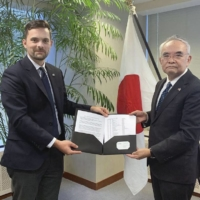 Paul Hastings (left), executive director of the Japan ICU Foundation, submits a petition to Kanji Yamanouchi, Japanese consul general in New York, on Thursday.