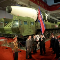 North Korean leader Kim Jong Un speaks to officials next to military weapons and vehicles on display, including the country's intercontinental ballistic missiles, at the Defense Development Exhibition, in Pyongyang on Oct. 12.